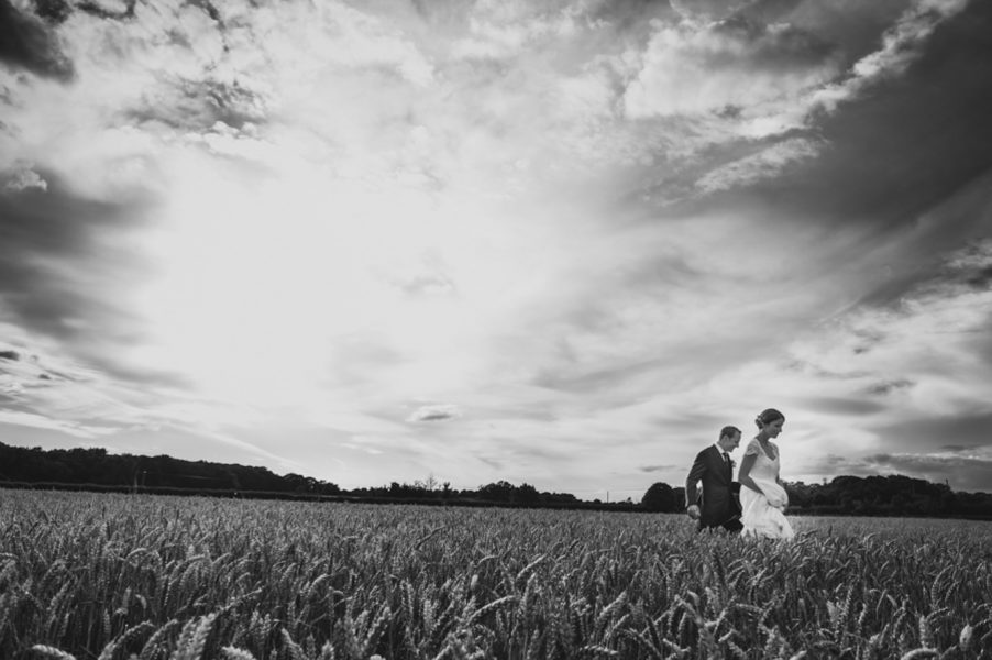 bride and groom walking through fields in oxford