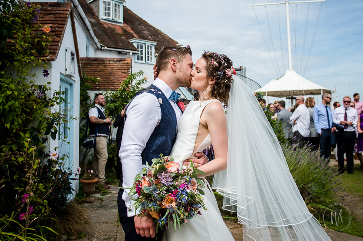 bride and groom kissing at itchenor sailing club