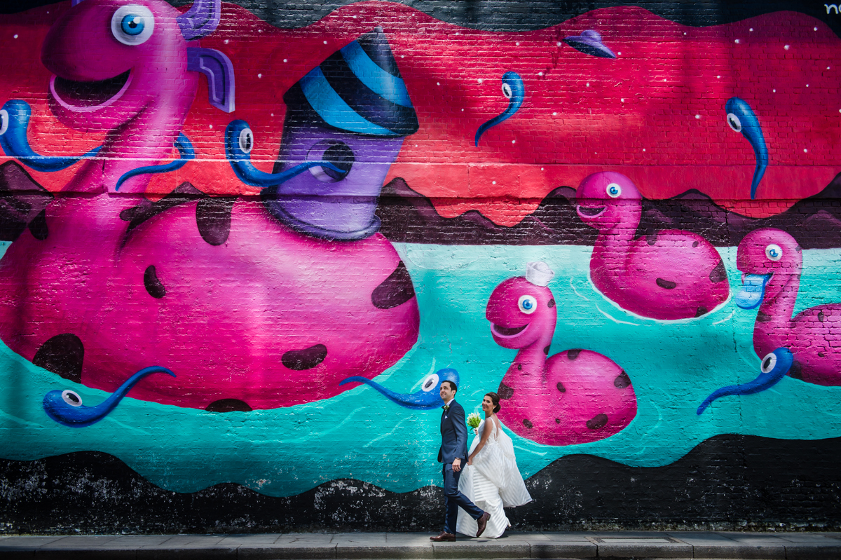 bride and groom walking in front of a graffiti wall